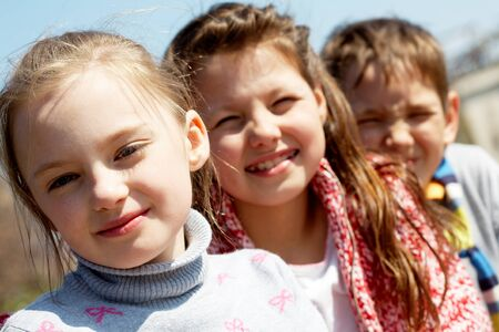 Portrait of smart preschoolers standing in row and looking at camera Stock Photo - 9820299
