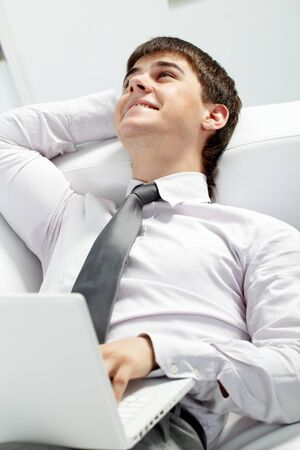 Image of young successful businessman sitting in office with laptop Stock Photo - 9807344