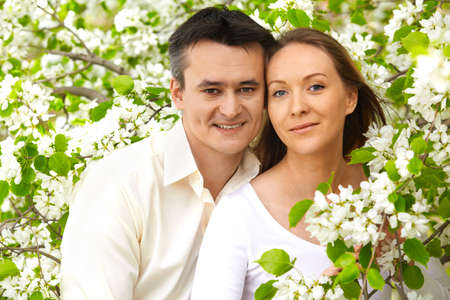 Portrait of young couple looking at camera among apple trees photo