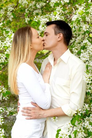 Portrait of young amorous couple kissing in park photo