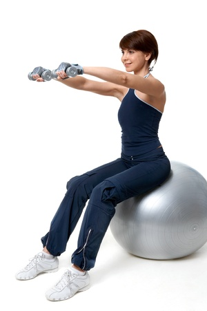 Image of smiling woman doing exercise with barbells on grey ball over white background photo