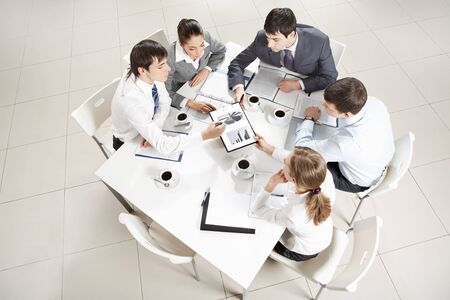 Above view of business team sitting around table and working with papers photo