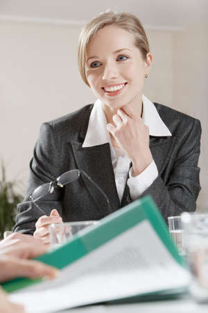Portrait of businesswoman listening to her colleague attentively photo