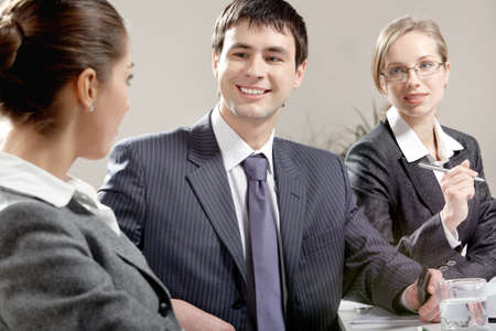 Portrait of happy businessman looking at colleague with another woman near by  Stock Photo - 9821833