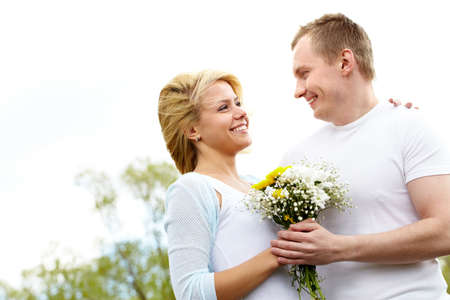 Laughing couple embracing and looking at each other outdoors photo