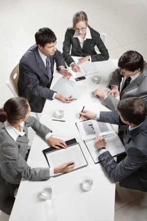 Team of five business people discussing an important question at briefing  photo