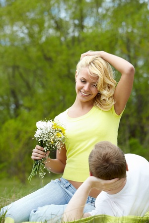 Happy woman with bunch of flowers and her boyfriend looking at each other in park Stock Photo - 9807128