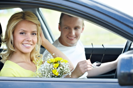 Happy woman with bunch of flowers looking at camera in the car Stock Photo - 9807131