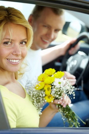 Happy woman with bunch of flowers looking at camera in the car photo
