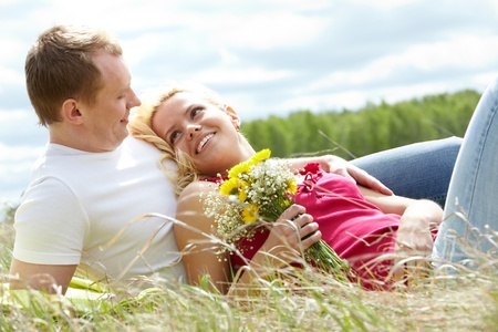 husband and wife: Happy woman with bunch of flowers and her boyfriend looking at each other in park