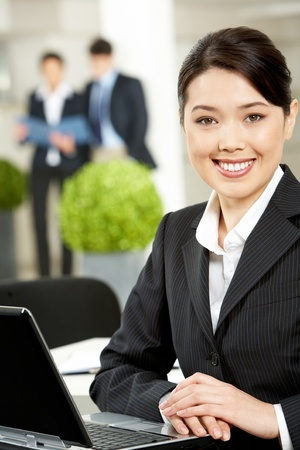 Portrait of pretty woman looking at camera with smile on the background of working partners photo