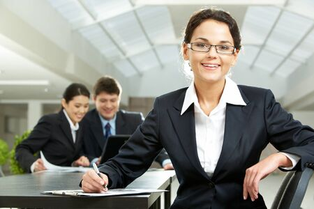 Portrait of pretty woman looking at camera in working environment photo