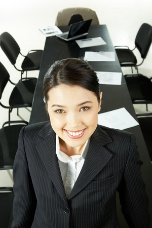 Portrait of pretty woman looking at camera with smile on the background of long table and chairs photo