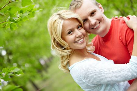 Portrait of young couple embracing and looking at camera outdoors photo