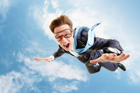 man flying: Conceptual image of young businessman flying with parachute on back Stock Photo