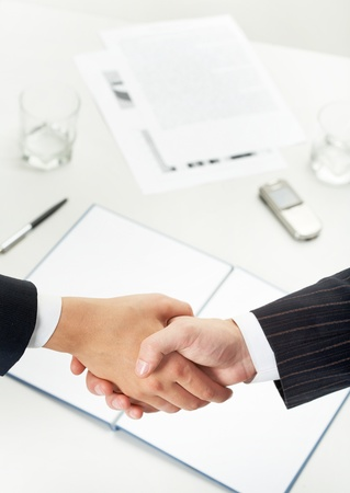 Photo of handshake of business partners after signing new contract photo