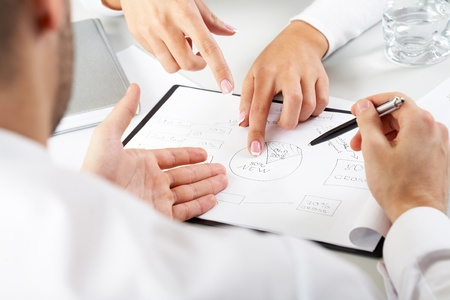 group strategy: Close-up of team working with documents at business meeting Stock Photo