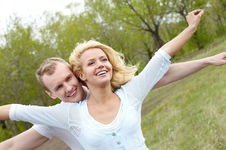 Portrait of happy couple stretching arms in natural environment photo