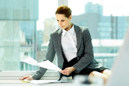 Photo of smart businesswoman working with papers in office photo