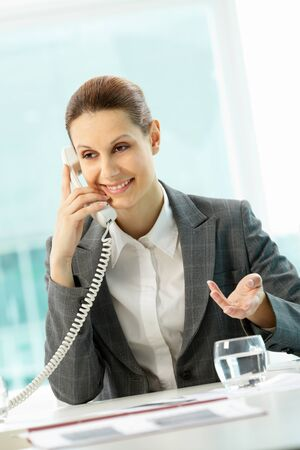 Photo of smiling businesswoman calling in office photo