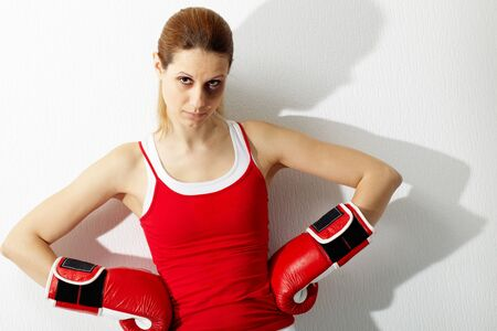 Portrait of young woman in red boxing gloves looking at camera  photo