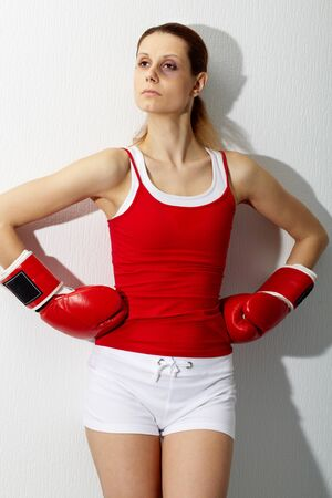 sportive: Portrait of young sporty woman in red boxing gloves looking aside