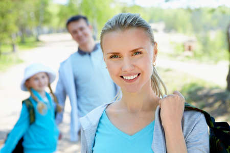 Portrait of pretty woman looking at camera with her family on background in summer photo