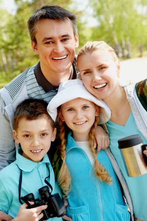 Portrait of family of travelers looking at camera in summer photo