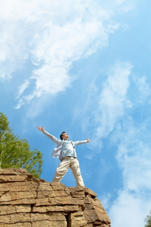Portrait of free man standing on cliff with stretched arms and enjoying hot day photo