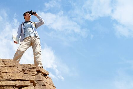 binoculars: Portrait of young man with binoculars standing on cliff and observing area