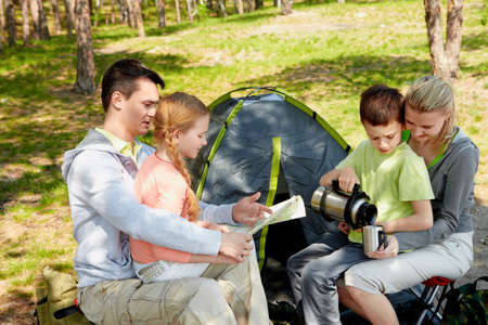 forest tea: Portrait of family of travelers spending time in forest with tent near by Stock Photo