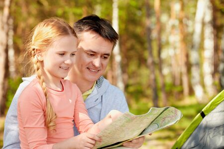 Portrait of father and his daughter looking at map while on trip photo