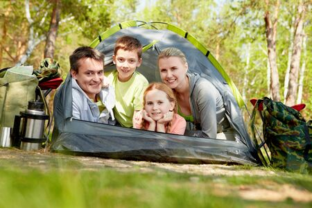 Portrait of family of travelers in tent looking at camera photo