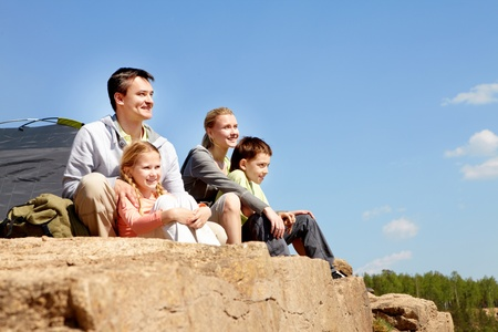 edge of cliff: Portrait of family of travelers sitting on rocky cliff