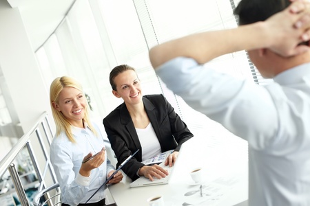 Portrait of confident businesswomen sharing ideas with colleague at meeting photo