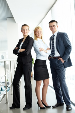 Portrait of friendly three business people looking at camera