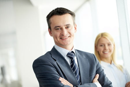 Portrait of friendly leader looking at camera with employee behind photo