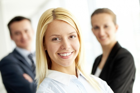 foreground: Portrait of friendly leader looking at camera with two employees behind