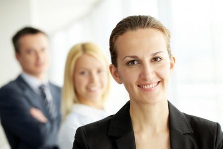 Portrait du leader jolie regardant la caméra avec deux partenaires derrière