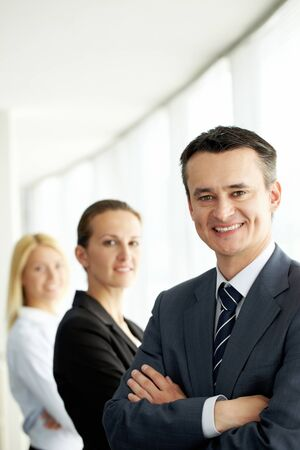 Portrait of friendly leader looking at camera with two employees behind photo
