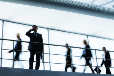 calling businessman: Businessman calling with walking people on background Stock Photo
