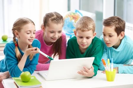 salon de clases: Retrato de colegialas inteligentes y escolares mirando el port�til en el aula
