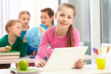 classmate: Portrait of smart schoolgirl sitting in classroom with her classmates on background Stock Photo