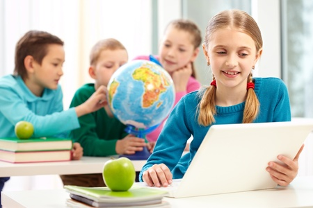 junior education: Portrait of smart schoolgirl working with laptop on background of her classmates Stock Photo