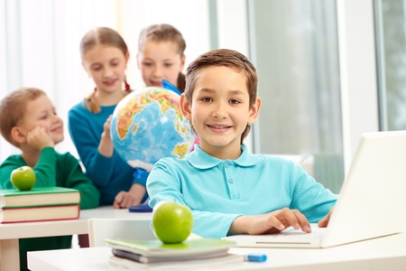 Portrait of smart schoolboy typing on laptop with classmates on background photo