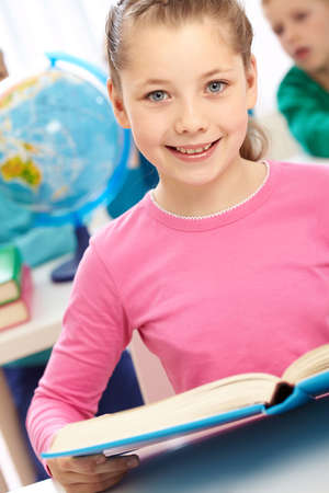 place to learn: Portrait of smart schoolgirl with open book looking at camera