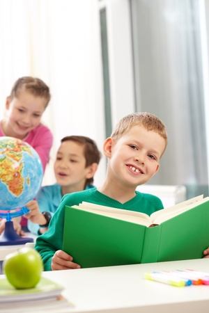 Cute schoolboy with book in class on background of classmates Stock Photo - 9820194