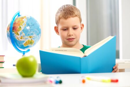 Cute schoolboy reading book in class during lesson photo