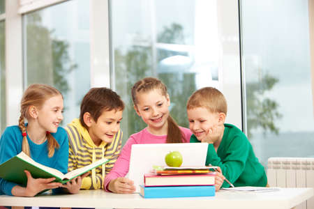 Portrait of smart schoolgirls and schoolboys looking at the laptop in classroom photo