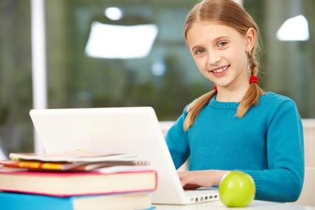 schulm�dchen: Portr�t von smart sch�lerin sitzend im Klassenzimmer und eingeben